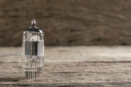 vacuum tube, old electronic component part on wooden surface and blur background