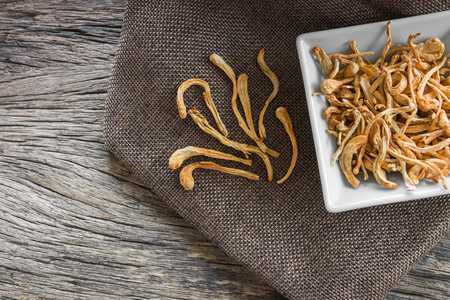dried cordyceps militaris mushroom with old and crack wooden surface background