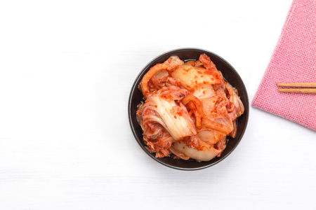 kimchi in ceramic dish on white wooden board with copy space, top view. healthy food concept.