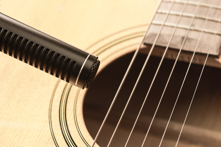 soft focus of condenser microphone with blurred acoustic guitar in vintage tone. music and sound record concept