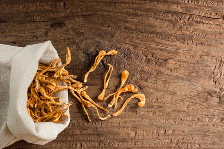 vue de dessus de champignons séchés cordyceps militaris avec sac en tissu sur la table en bois vieux et fissure, alternative saine alimentation et concept médical. Banque d'images