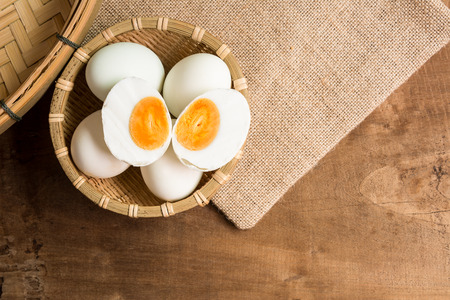 top view of salted duck egg in bamboo basket on old wooden table in kitchen with copy space. food preservation concept. 스톡 콘텐츠
