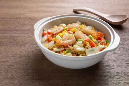 close up of fried rice with shrimp in a ceramic bowl on wooden table. homemade style food concept.