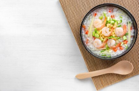 top view of boiled rice clear soup with shrimp in a ceramic bowl on wooden table. homemade style food concept. Stock fotó