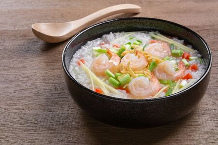 close up of boiled rice clear soup with shrimp in a ceramic bowl on wooden table. asian homemade style food concept. Stock fotó