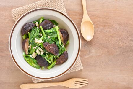 top view of stir fried chinese kale and shiitake mushroom with soy sauce in a ceramic dish on wooden table.  healthy homemade style food concept. Stockfoto