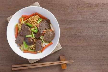 top view of hot and spicy stir fried instant noodle with beef and vegetable in a ceramic plate on wooden table. asian homemade style food concept.