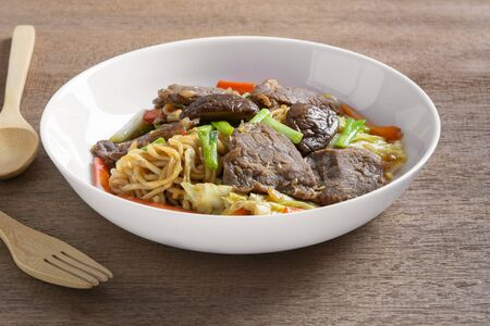 hot and spicy stir fried instant noodle with beef and vegetable in a ceramic plate on wooden table. asian homemade style food concept.