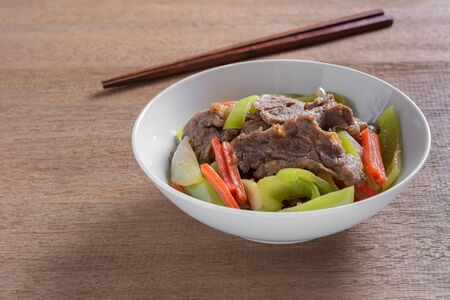 stir fried beef with banana pepper in a ceramic bowl on wooden table. hot and spicy homemade style food concept.