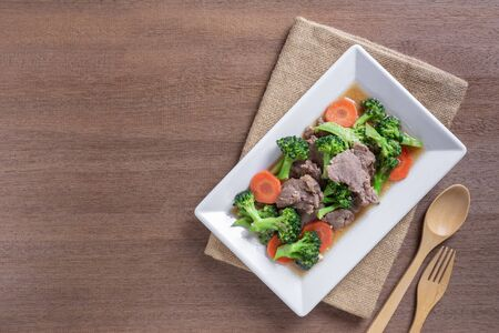 top view of stir fried beef and broccoli in a plate on wooden table. homemade style food concept.