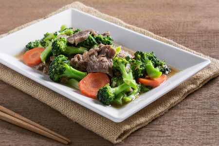 stir fried beef and broccoli in a plate on wooden table. homemade style food concept.