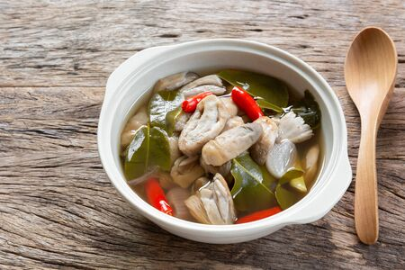 close up of spicy straw mushroom clear soup in a ceramic bowl on wooden table. asian homemade style healthy food concept.