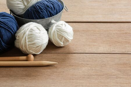 close up of yarn and knitting needles on wooden table in vintage tone, copy space. hobby and leisure concept.