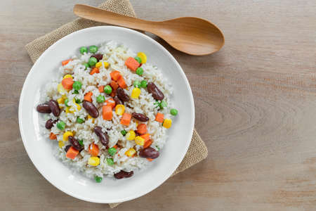 top view of fried rice with vegetable in a ceramic dish on wooden table. homemade style food concept. Reklamní fotografie