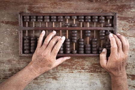 economic revival: old abacus and hand on wooden background Stock Photo