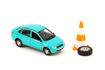The car toy, the cone and the emergency spare wheel on a white background. Concept Stock Photo
