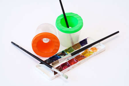 capacities: Three brushes for drawing by a water colour, a palette with paints and two capacities for water Stock Photo