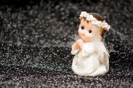Doll of a praying angel of the keeper on a dark, star background photo