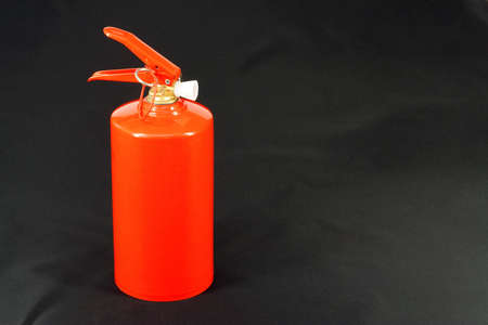 extinguishing: A red fire extinguisher on a black background. Hand tools for fire extinguishing