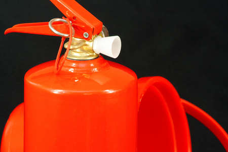 extinguishing: A red fire extinguisher and a bucket of red on a black background. Devices for extinguishing