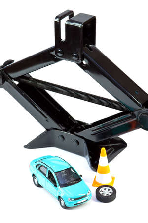 Car jack, car, emergency cone and spare wheel on a white background. Concept photo