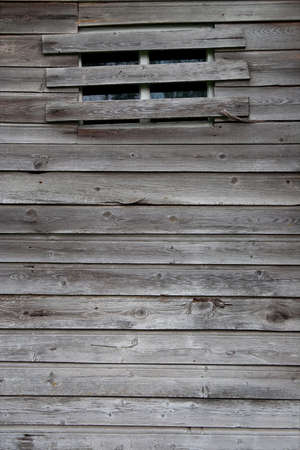 Wooden wall of the old rustic barn with a window. Texture, background Stock Photo
