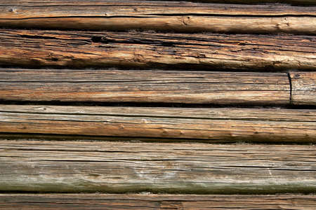 log wall: The log wall of the old village house in the Russian north. Texture, background