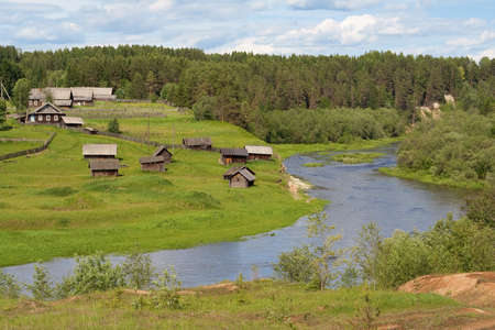 The old village in the forest with the river in the Russian north
