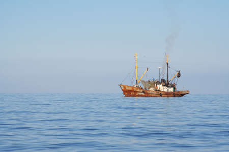 mining ships: Fishing boats while fishing in the evening sea Stock Photo
