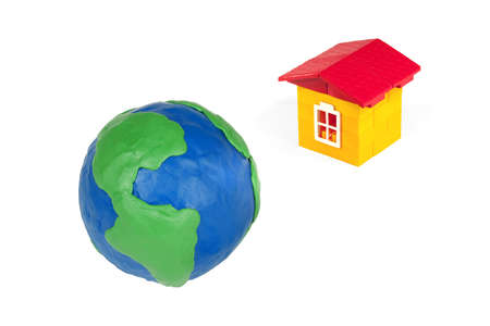 Globe of the earth made of clay and toy house on a white background photo