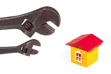 Two old wrench and a toy house with a white background photo