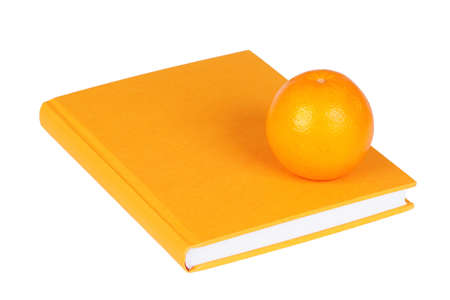 Big yellow book and an orange on a white background photo