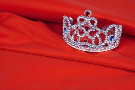 Crown toy lying on the red, the tissue background Stock Photo - 9027550