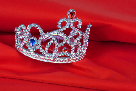 Crown toy lying on the red, the tissue background photo