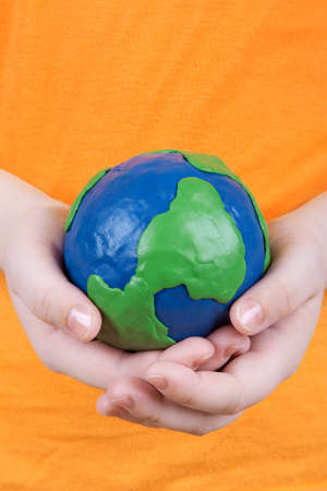 Childrens hands holding a plasticine model of the globe of the earth  photo