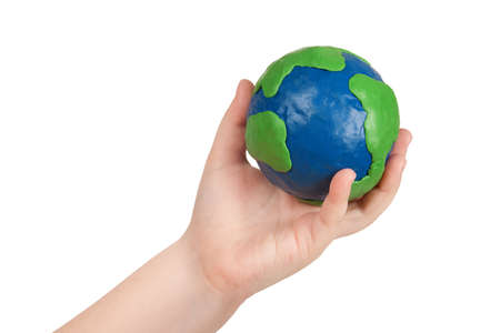 Childs hand holding a plasticine model of the globe of the earth  photo