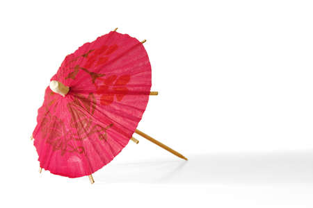 Red paper umbrella for cocktails, lying on a white background