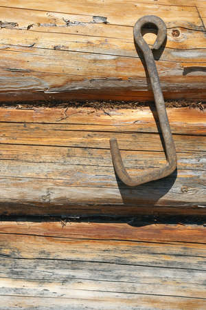 Fragment of wooden frame wall with an iron hook. Texture, background photo