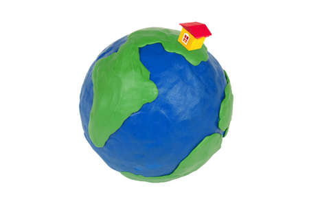 Plasticine globe and toy house on a white background photo