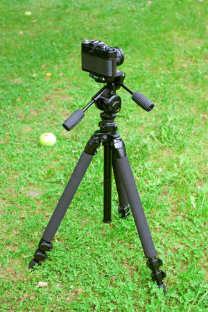 tripod mounted: The camera is mounted on a tripod, standing on the grass