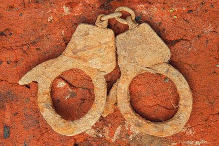 cadena rota: Los viejos, oxidados, esposas de metal en el suelo de ladrillo