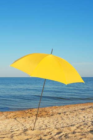 beach umbrella: Yellow parasol, standing on the shore of the evening sea Stock Photo