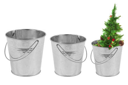 Three metal bucket and a Christmas tree on a white background photo