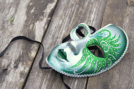Festive carnival mask lying on a wooden sidewalk photo