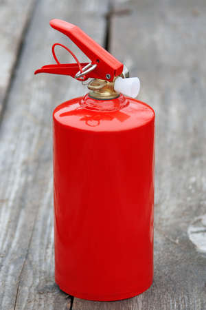 treated board: The compact fire extinguisher, which stands on an old wooden sidewalk