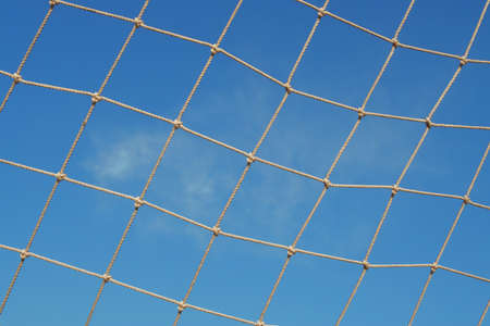 Athletic mesh stretched on a background of blue sky  The texture of the background photo