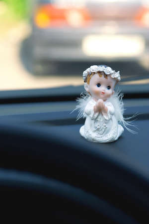 Figurine praying guardian angel in the car