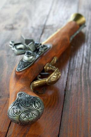 Pistolet ancien modèle allongé sur une table en bois Banque d'images - 15446145
