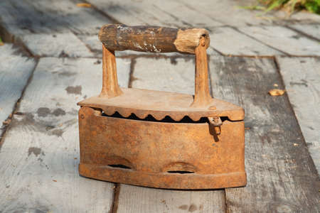 treated board: Old coal iron, standing on a wooden sidewalk Stock Photo