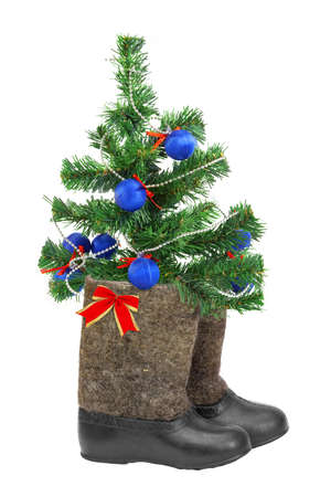 Decorated Christmas tree and boots on a white background photo